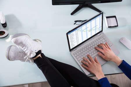 Foto de Businessperson's Hand Working On Gantt Chart Using Laptop With Crossed Legs On Office Desk - Imagen libre de derechos