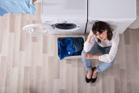 Foto de Upset Woman Sitting At Laundry Room Besides Basket Full Of Dirty Clothes - Imagen libre de derechos