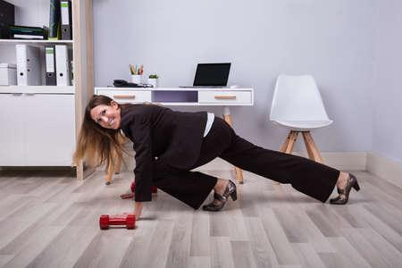 Photo pour Photo Of Businesswoman Doing Pushups On Hardwood Floor - image libre de droit