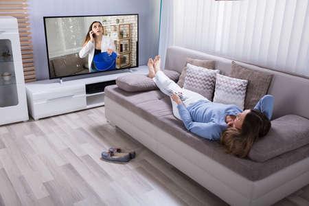 Foto de Woman Lying On Sofa Using Calculator While Watching Television At Home - Imagen libre de derechos
