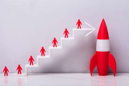 Photo for Red Human Figurine Standing On White Increasing Arrow Graph Near Red Rocket - Royalty Free Image