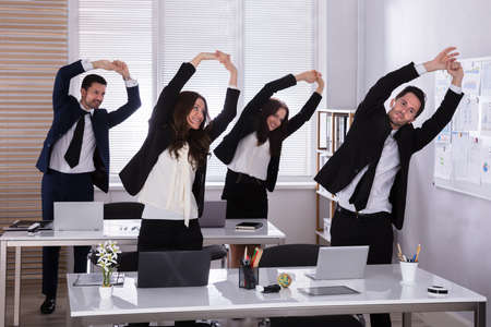 Photo pour Happy Businesspeople Doing Stretching Exercise Behind Desk At Workplace - image libre de droit
