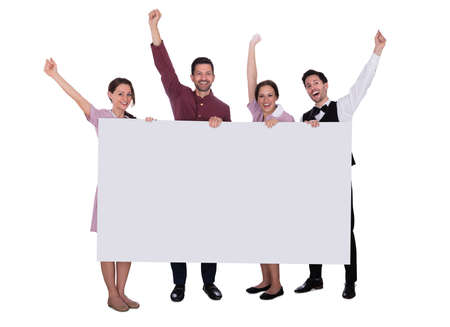 Photo pour Excited Young Male And Female Staff Holding Billboard Raising Their Arms On White Background - image libre de droit