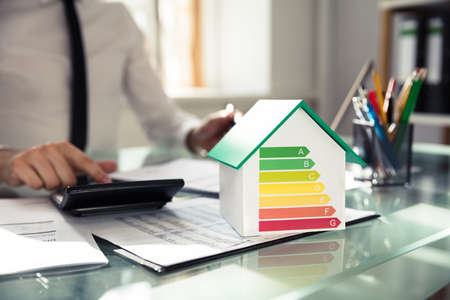 Photo for Close-up Of House Model Showing Energy Efficiency Rate In Front Of Businessperson's Hand Using Calculator - Royalty Free Image