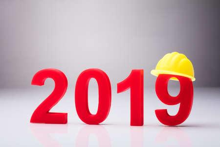 Foto de Year 2019 With Yellow Hardhat Over White Background - Imagen libre de derechos