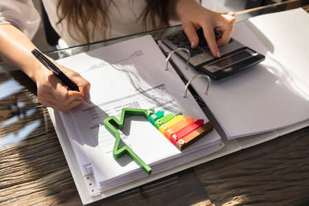 Photo pour Woman Calculating Invoice With Energy Efficient Chart And House Silhouette In Office - image libre de droit