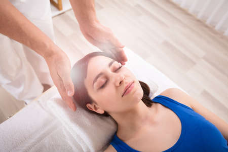 Foto de Close-up Of Therapist's Hand Performing Reiki Treatment On Young Woman In Spa - Imagen libre de derechos