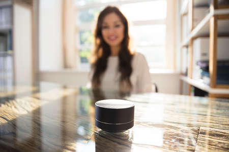 Photo pour Close-up Of Wireless Speaker In Front Of Businesswoman Listening To Music - image libre de droit