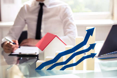 Foto de Close-up Of Increasing Blue Arrows And Graph In Front Of House Model - Imagen libre de derechos