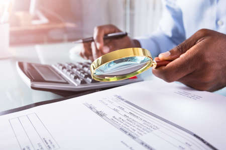 Photo for Close-up Of A Businessman Holding Magnifying Glass Over Invoice Using Calculator - Royalty Free Image