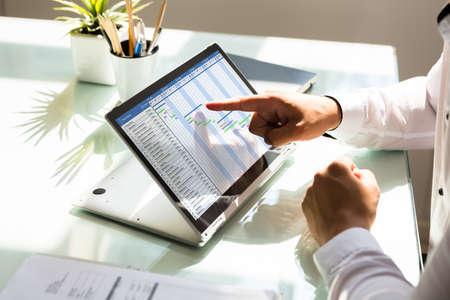Foto de Businessman's hand analyzing gantt chart on laptop over reflective desk - Imagen libre de derechos