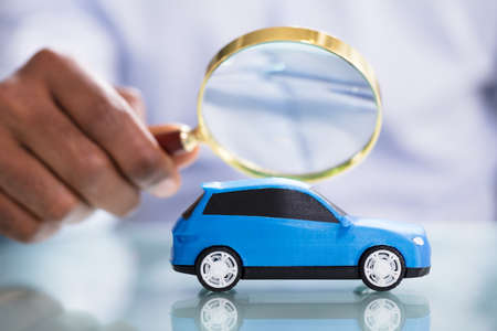 Photo for Close-up Of A Person's Hand Holding Magnifying Glass Looking Blue Toy Car - Royalty Free Image