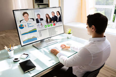 Foto de Young businessman videoconferencing with his partners on computer - Imagen libre de derechos