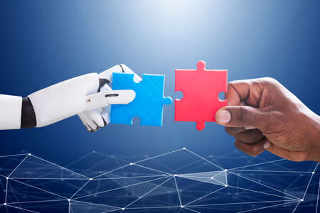 Photo for Robot And Human Hand Joining Red And Blue Jigsaw Over The Blue Digital Background - Royalty Free Image