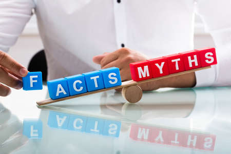 Photo pour Businessman's hand showing unbalance between facts and myths on wooden seesaw - image libre de droit