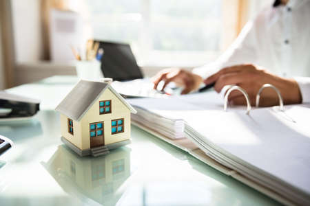 Photo for Businessman's hand calculating invoice with house model in office - Royalty Free Image
