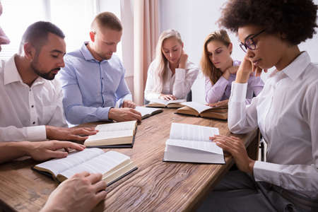 Photo for Group Of Young Multiethnic People Reading Bible Over Wooden Desk - Royalty Free Image