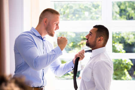 Photo for Side View Of A Angry Young Businessman Fighting With His Coworker - Royalty Free Image