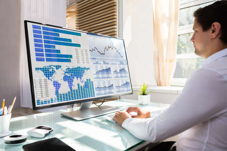 Foto für Young male stock market broker analyzing graph on computer at workplace - Lizenzfreies Bild