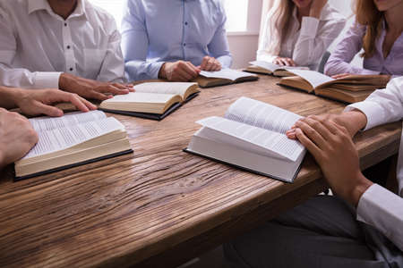 Foto de Group Of People Reading Bible On Wooden Desk - Imagen libre de derechos