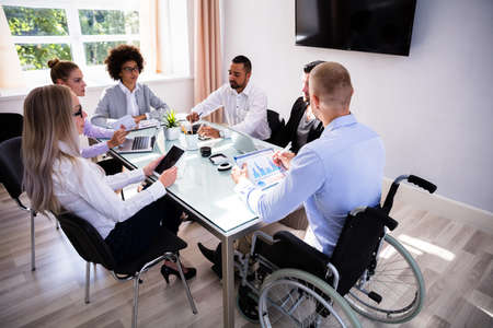 Foto de Disabled Male Manager Sitting With His Colleagues At Workplace - Imagen libre de derechos