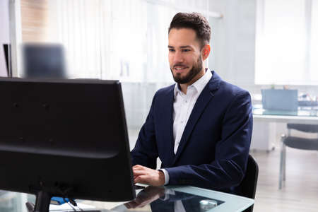 Photo for Smiling Young Businessman Using Computer In Office - Royalty Free Image