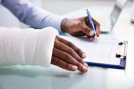 Photo pour Overhead View Of Injured Man With Bandage Hand Filling Insurance Claim Form On Clipboard - image libre de droit