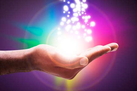 Foto de Glowing Lights Flowing From An Open Hand Against Colorful Circle Backdrop - Imagen libre de derechos