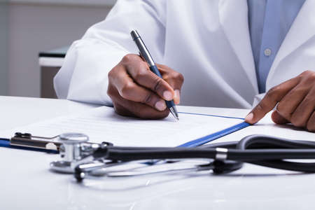 Photo pour Stethoscope In Front Of Doctor Filling Form With Pen Over The Desk - image libre de droit