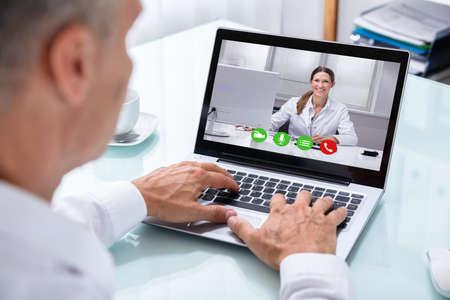 Foto de Businessman's Hand Videoconferencing With Happy Female Doctor On Laptop - Imagen libre de derechos