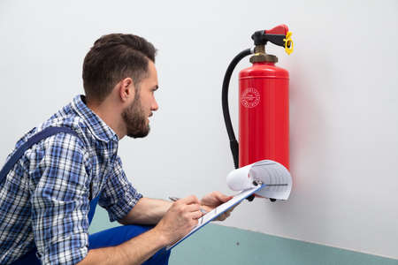 Photo pour Close-up Of A Young Male Technician Checking Fire Extinguisher Writing On Document - image libre de droit