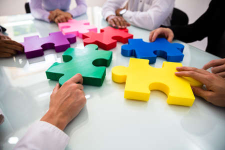 Photo for Group Of Businesspeople Colorful Solving Jigsaw Puzzle On Desk In Office - Royalty Free Image