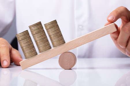 Photo pour Human Hand Balancing Golden Stacked Coins On Wooden Seesaw - image libre de droit