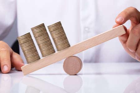 Foto de Human Hand Balancing Golden Stacked Coins On Wooden Seesaw - Imagen libre de derechos