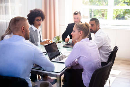 Photo pour Group Of Businesspeople Sitting In Office During Business Meeting - image libre de droit