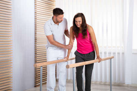 Photo pour Therapists Assisting Female Patient In Walking With The Support Of Handrails - image libre de droit