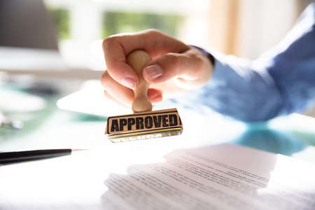 Photo pour Close-up Of A Businesswoman's Hand Stamping On Approved Contract Form - image libre de droit