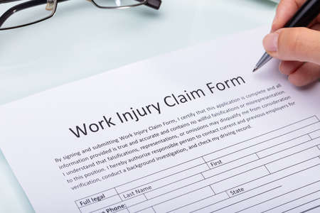 Photo pour Close-up Of A Woman's Hand Filling Work Injury Claim Form - image libre de droit