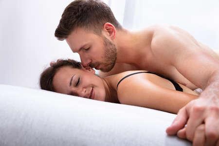 Photo pour Romantic Young Couple Being Intimate On Bed - image libre de droit