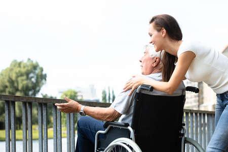 Foto de Young Woman With Her Disabled Father Near Railing At Outdoors - Imagen libre de derechos