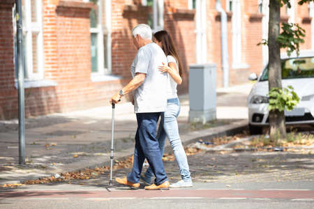 Photo pour Side View Of A Young Woman Assisting Her Father While Crossing Road - image libre de droit