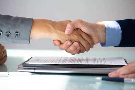 Photo for Business Partners Shaking Hands Over Contract Form - Royalty Free Image