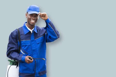 Foto de Portrait Of A African Male Pest Control Worker With Pesticide Sprayer - Imagen libre de derechos