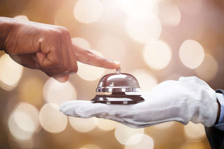 Photo pour Customer's Hand Ringing Service Bell Held By Butler On Bokeh Background - image libre de droit