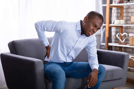 Foto de Young African Man Sitting On Sofa Having Back Pain - Imagen libre de derechos