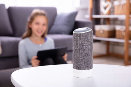 Photo pour Close-up Of A Wireless Speaker On Furniture With Girl In Background - image libre de droit
