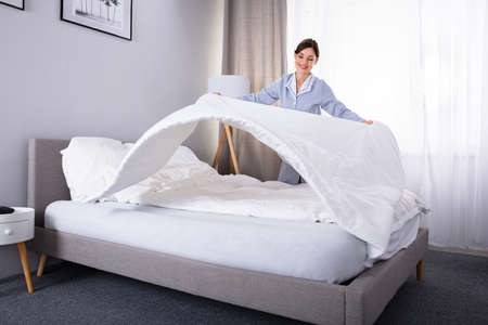 Photo pour Smiling Young Female Housekeeper Arranging Bedsheet On Bed In Hotel Room - image libre de droit