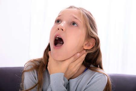 Photo pour Portrait Of A Girl Unable To Breathe Pressing Her Neck - image libre de droit