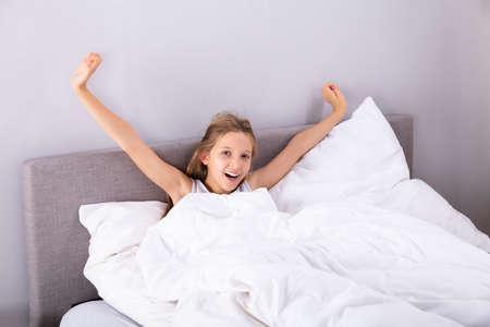 Foto de Portrait Of A Girl Sitting On Bed Stretching Her Arms In Bedroom - Imagen libre de derechos