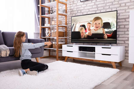 Photo pour Girl Sitting On Carpet Watching Television At Home - image libre de droit